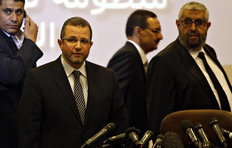 "Egypt's Prime Minister Hisham Kandil (2nd L) is seen with Sherif Haddara (R), Minister of Petroleum at news conference about a new ""smart ca"
