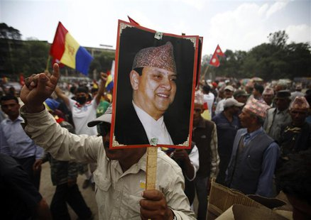 A supporter of the Rastriya Prajatantra Party Nepal (RPP-Nepal) holds a portrait of former King Gyanendra Shah during a protest rally in Kat
