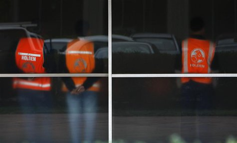 Workers wearing safety vests are seen through frosted windows at the General Motors Holden offices in Melbourne in this June 2, 2009 file ph