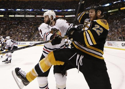 Boston Bruins right wing Shawn Thornton (22) is hit into the boards by Chicago Blackhawks defenseman Brent Seabrook (7) in Game 3 of their N