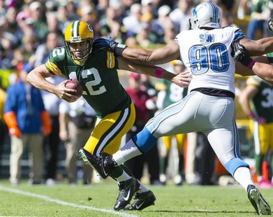 Green Bay Packers quarterback Aaron Rodgers (12) runs with the ball in front of Detroit Lions defensive tackle Ndamukong Suh (90) during the