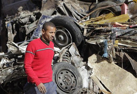 A man walks near a damaged vehicle after an explosion near a security building in Egypt's Nile Delta city of Mansoura in Dakahlyia province,