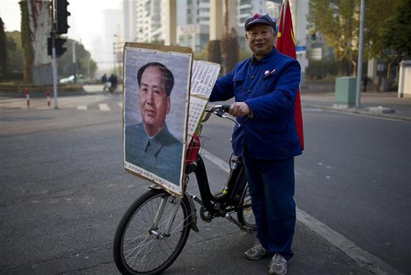 Qiu, a 65-year-old retired shipyard worker wearing a Red Army hat, poses for a photograph with his bicycle bearing a portrait of China's lat