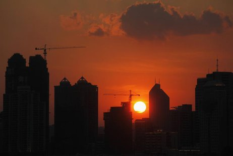The sun sets behind buildings under construction in Guangzhou, Guangdong province July 4, 2010. REUTERS/Joe Tan