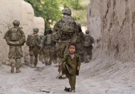 A boy plays on a street as U.S. Army soldiers of the Battle company, 1-508 Parachute Infantry battalion, 4th Brigade Combat Team, 82nd Airbo