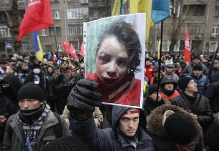 A protester holds a picture of journalist Tetyana Chornovil, who was beaten and left in a ditch just hours after publishing an article on th