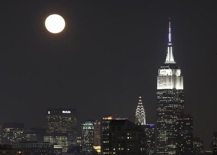 The moon rises behind the skyline of New York and the Empire State Building (R), as seen from Jersey City, New Jersey, December 18, 2013. RE