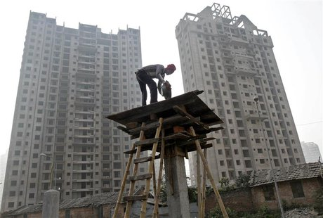 A labourer works at the construction site of a residential complex in Kolkata December 21, 2013. India's biggest cities face a worsening sho