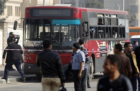 A member of the media films a damaged bus after a bomb blast near the Al-Azhar University campus in Cairo's Nasr City district December 26,