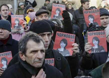 Protesters hold pictures of journalist Tetyana Chornovil, who was beaten and left in a ditch just hours after publishing an article on the a