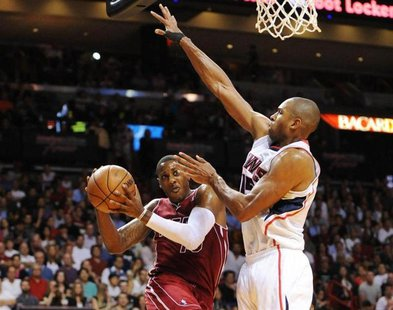 Dec 23, 2013; Miami, FL, USA; Miami Heat point guard Mario Chalmers (15) is defended by Atlanta Hawks center Al Horford (15) under the baske