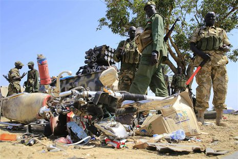 South Sudan army soldiers stand next to a destroyed motorcycle near Bor Airport, 180 km (108 miles) northwest from capital Juba December 25,