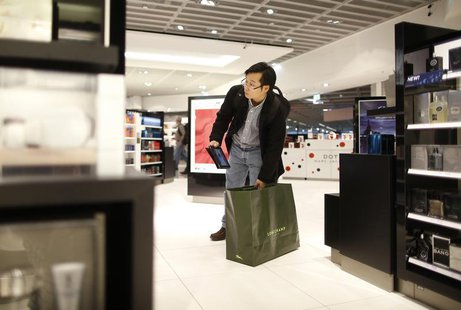A man with a tablet computer stands in a Duty Free store at the Fraport airport in Frankfurt November 14, 2012. REUTERS/Lisi Niesner