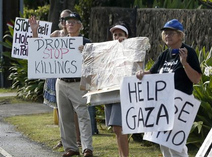 Protesters hold signs as the motorcade of U.S. President Barack Obama returns to Obama's vacation home in Kailua, Hawaii December 28, 2013.