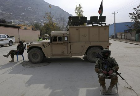 Afghan National Army (ANA) soldiers keep watch near a building in which the Loya Jirga (or grand council) is holding a committee session, in