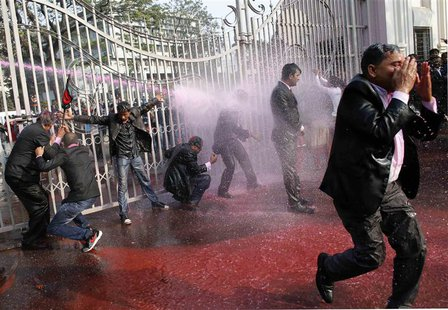 Lawyers loyal to Bangladesh Nationalist Party (BNP) and Bangladesh Jamaat-E-Islami shout slogans as policemen use water cannons during a pro