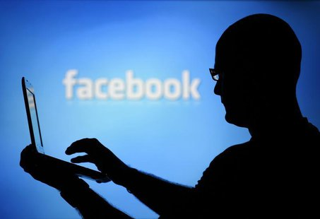 A man is silhouetted against a video screen with an Facebook logo as he poses with an Dell laptop in this photo illustration taken in the ce