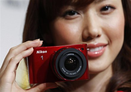 A model poses with Nikon Corp's new Nikon 1 J1 camera at its unveiling ceremony in Tokyo, in this September 21, 2011 file photo. REUTERS/Kim