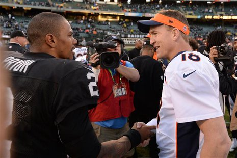 December 29, 2013; Oakland, CA, USA; Denver Broncos quarterback Peyton Manning (18) shakes hands with Oakland Raiders quarterback Terrelle P