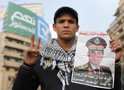 A supporter of Egypt's army chief and defense minister General Abdel Fattah al-Sisi holds a poster with Sisi's image during a protest in sup