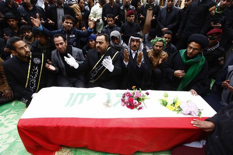 Mourners pray near the coffin of a soldier, who was killed during the clashes in Ramadi during the funeral in Najaf, 160 km (99 miles) south