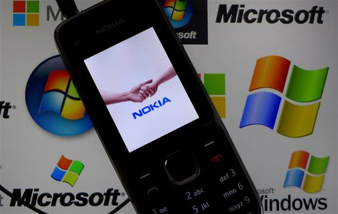 A Nokia mobile phone lies on a tablet computer showing logos of Microsoft, in this illustration picture taken in Frankfurt, November 18, 201