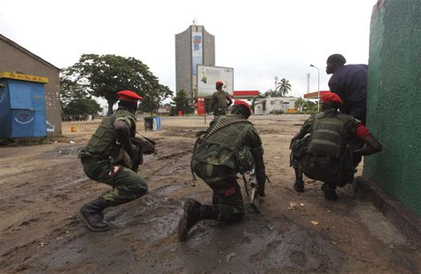 Congolese security officers position themselves as they secure the street near the state television headquarters (C) in the capital Kinshasa