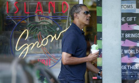 U.S. President Barack Obama carries a shave ice out of Island Snow near his vacation home in Kailua, Hawaii December 31, 2013. REUTERS/Kevin