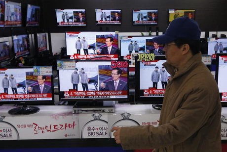 A man walks past televisions showing reports on the execution of Jang Song Thaek, who is North Korean leader Kim Jong Un's uncle, at an elec
