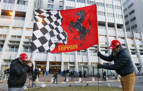 Fans fix a Ferrari flag in the ground in front of the CHU Nord hospital emergency unit in Grenoble, French Alps, where retired seven-times F