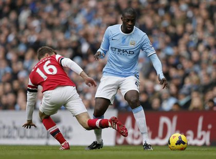 Manchester City's Yaya Toure (R) is challenged by Arsenal's Aaron Ramsey during their English Premier League soccer match at the Etihad stad
