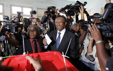 Madagascar's presidential candidate Hery Rajaonarimampianina (C) holds his ballot before casting his vote at a polling centre in Tsimbazaza