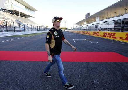 Lotus F1 Formula One driver Kimi Raikkonen of Finland walks on the track at the Suzuka circuit October 10, 2013, ahead of Sunday's Japanese