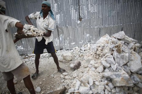 A worker helps his colleague to lift a bucket of limestone as they work in a stone crushing factory at Burimari in Lalmonirhat district July