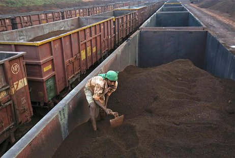 A worker levels the iron ore in a freight train at a railway station at Chitradurga in the southern Indian state of Karnataka in this Novemb