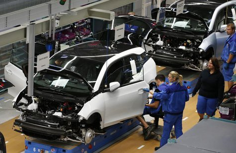 Workers assemble BMW i3 electric cars at the production line of the BMW factory in Leipzig September 18, 2013. REUTERS/Fabrizio Bensch