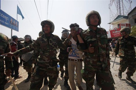 Cambodian soldiers escort a worker who had been taking part in a protest after clashes broke out, on the outskirts of Phnom Penh January 2,
