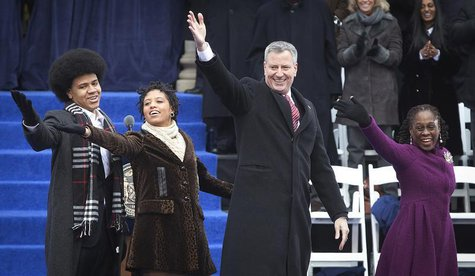 New mayor Bill de Blasio (2nd R) and his wife Chirlane de Blasio (R) blow a kiss to the crowd with their son Dante de Blasio (L) and daughte