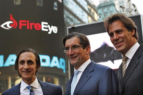 FireEye Inc. Chairman of the Board, David DeWalt (R) and Founder Ashar Aziz (L) pose with Nasdaq CEO Robert Greifeld outside the Nasdaq Mark