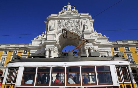 Passengers inside a tram pass in front of the main arch of Praca do Comercio square where the Finance Ministry is located, in Lisbon Septemb