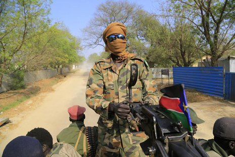 A South Sudan army soldier mans a machine gun, that has been mounted onto a truck, as it drives through a street in Malakal town, 497 km (30