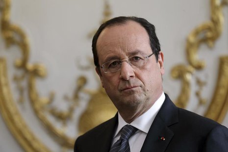 French President Francois Hollande listens to the speech of French Prime Minister during a new year ceremony with members of the government