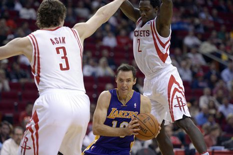 Los Angeles Lakers point guard Steve Nash (10) drives against Houston Rockets center Omer Asik (3) and point guard Patrick Beverley (2) duri