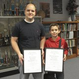 Random Lake Middle School student Reilly McMullen (right) and art teacher Brian Sommersberger (left) pose with their respected plaques honoring their choice as a W.T. Graham Youth Art Award winner for 2013.