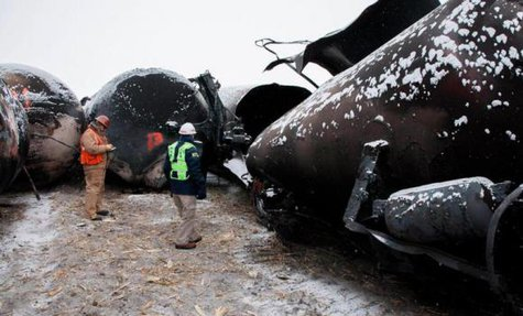 National Transporation and Safety Board (NTSB) member Robert Sumwalt (R) views damaged rail cars at the scene of the BNSF train accident in Casselton, North Dakota January 1, 2014 in this handout provided by NTSB. CREDIT: REUTERS/NTSB/HANDOUT VIA REUTERS