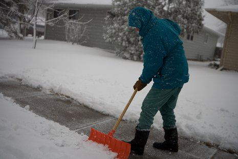 A man shovels snow off a sidewalk.