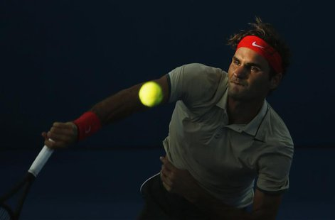 Roger Federer of Switzerland serves to Jeremy Chardy of France during their men's singles semi-final match at the Brisbane International ten