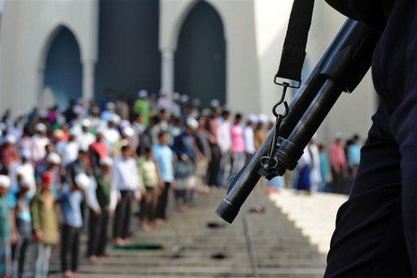 People take part in Friday prayers as members of the police stand guard in Dhaka January 3, 2014. REUTERS/Stringer