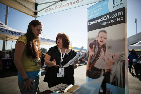 Maria Franco (R) explains health insurance to Violet Lucas-Barajas, 28, at an event to inform people about the Affordable Care Act and donat