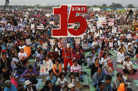 A supporter of Puea Thai party carries a sign with the number 15, referring to the party's number during upcoming elections, poses for photo
